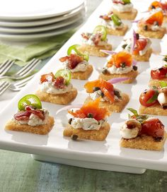 Buttery cheddar cheese shortbread crackers are topped three different ways - candied bacon and goat cheese, lox-inspired, and balsamic roasted tomatoes. There's sure to be a topping to please everyone at your next party.