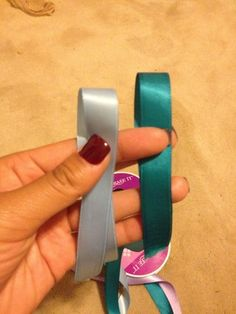 Take each end and overlap the ribbon causing to make a loop #1: teal ribbon #2: light blue ribbon