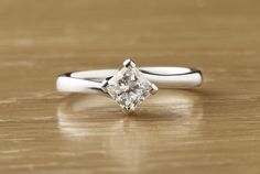 Modern classic princess cut diamond solitaire engagement ring with a 4 claw twist setting and squared claws.