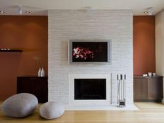 stone clad fireplace to the ceiling, TV above, closed built-in on right side, accent color on the wall