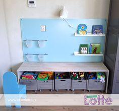 De achterwand is een plaat mdf en het tafeltje is van een meubelpaneel met steigerhoutprint gemaakt (beide Gamma). De bakjes hangen aan twee handgrepen voor keukenkastjes en de boekjes staan op twee houders voor schilderijen (alles Ikea). De kistjes voor het speelgoed zijn van de Xenos. De wieltjes (Gamma) zijn eronder gemaakt zodat ze makkelijk te verplaatsen zijn. Het lampje is ook van Ikea. De mdf plaat is geschilderd in de kleur 'korenbloem' van de Gamma.