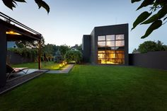 In general, physical form of building is divided into two parts with similar shapes and sizes The first cube facade is revetted with plaster embroidered in the form of squares and second is decorated with clad in black-painted wooden panels with horizontal line structure. Transparent glass windows at front wall house offer green view of the garden, House has 105 sqm and held in a mixture of wood and concrete.