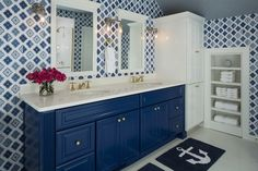 White and blue bathroom with Christian Lacroix Alcazar Cobalt Wallpaper over white penny tiled floors layered with navy blue anchor bath mats placed in front of a blue double vanity painted Benjamin Moore Down Pour Blue accented with brass pulls alongside an off- white counter which frames dual oval shaped sinks paired with brass faucets.
