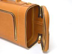メイン収納部は本体横のコの字型ファスナーで開閉し、両サイドに別の部屋がついているという他にはない3部屋構造、ギミックが効いた箱型革鞄。堅牢な手持ちとストラップで肩掛けもできます。