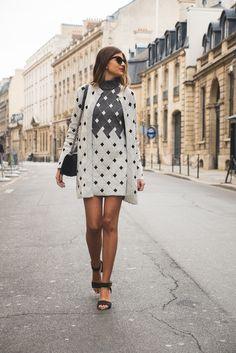 Mariana Cassou, sócia do Gallerist, com vestido e sobretudo de tricot gráfico preto e branco Coven, sandalia preta e bolsa a tiracolo preta. Street style Paris Fashion Week.