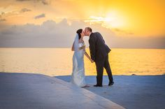 A bride and groom sharing a kiss while the sun sets. Photo by St. Vincent and the Grenadines Destination Wedding Photographer