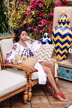 Summer getaway essentials - stylish travel outfit. Pair an embroidered dress with fun pom pom sandals and a raffia tote