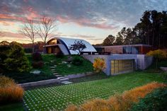"""The house is very different and exciting, but looks a little like an airport terminal :} The best idea here, however, is the """"driveway"""" which appears to be largely grass, and the non-lawn front yard and semi-primitive steps up to the entryway."""