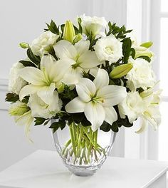 From the Vera Wang collection. Exuding a soft sophistication, this bouquet of white Asiatic Lilies and double lisianthus are brought together with fresh, lush greens and arranged to perfection in a clear modern glass vase, creating a beautiful way to offer an expression of grace and elegance. We Deliver Nationanwide! @Veldkamps