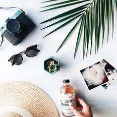 tana gandhi flatlay photography | sunglasses hat palm photos