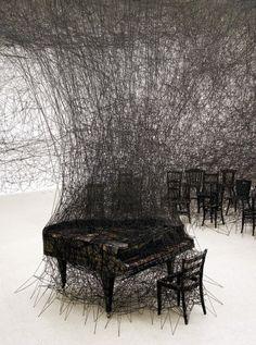 In Silence, installazione di  Chiharu Shiota. L'artista giapponese ha voluto ricordare un drammatico evento della sua infanzia quando la casa dei vicini andò a fuoco e bruciò quasi completamente lasciando il relitto di un pianoforte carbonizzato.