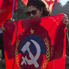 A woman holds a Chilean Communist Party flag while standing before the grave of the late Nobel Prize-winning poet…