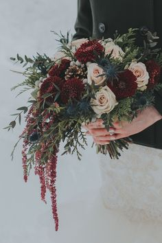 A winter bridal bouquet for a wedding at Emerald Lake Lodge with hanging burgundy amaranthus, pomponis, silver brunia, navy thistle, Quicksand roses and winter foliage! Photo: http://enterthekingdom.ca/ Bouquet: www.flowersbyjanie.com