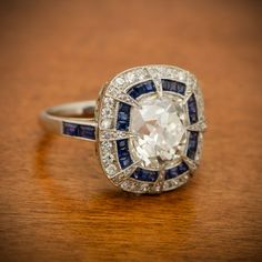 A beautiful and rare one-of-a-kind Antique Cushion Cut Diamond Engagement Ring. A double halo of diamonds and sapphires. Amazing.