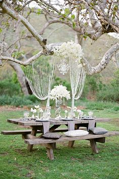 rustic backyard wedding decoration table and benches made of gray wood with pillows and napkins white flowers and elegant garlands julie hanan design