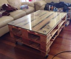Make a  sofa coffee table from wood pallets and glass.