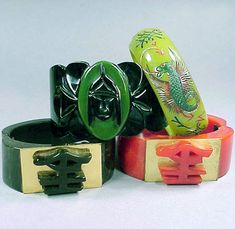 Group of Four Bakelite Hinged Bracelets  Each in the Oriental taste, two with similar metal mounted decoration. Widest 1 7/8 inches.    Sold for 1,600 (Includes Buyer's Premium)  Estimate 600-800
