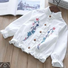 For a casual and formal day out, this embroidered white shirt is perfect! The colorful embroidery on the shirt are the highlights of the shirt. The top of the shoulder part is prettified with a ruffled furbelow. Baby Dress Tutorials, Baby Girl Dress Patterns, Baby Dress Design, Baby Clothes Patterns, Kids Dress Wear, Dresses Kids Girl, Kids Outfits, Cotton Frocks For Kids, Stylish Dress Designs