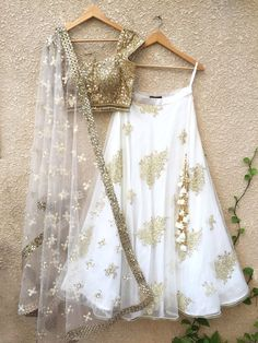 Gold mirror work blouse with tassels, teamed with white net lehenga with raw silk underlay and Pearl Butis, and net dupatta with white threadwork butis and mirror border workrlay. Handwork on lehenga and dupattaCan be colour customisedAll prod. Indian Lehenga, Lehenga Choli, Net Lehenga, Gold Lehenga, Lehenga Blouse, Lehenga White, Indian Attire, Indian Wear, Indian India