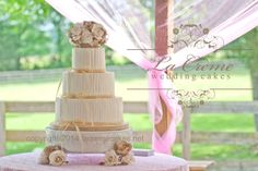 A rustic buttercream wedding cake with raffia ribbon and burlap rose topper.