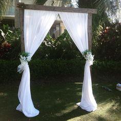 Wedding ceremony - dark wooden plank archway with chiffon curtains