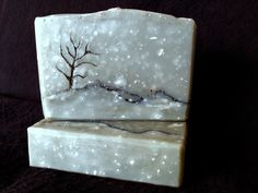 Snowy Winter's Night. Intrigued by Auntie Clara's use of water discount as a design tool, and her use of fine salt in the batter to make her dappled bar, I decided to create a snowy night scene using two layered in-the-pot swirls, separated by a charcoal pencil line, and enhanced by the crisp scent of a wonderful essential oil blend of peppermint, patchouli, cedar wood, and a bit of lemon to round it all out. I ended up adding a charcoal tree - the cedar wood eo just called for it to be…