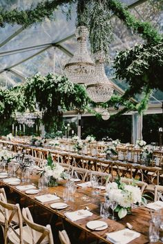 Luxurious wedding dinner reception in a clear-roof marquee with crystal chandeliers and lush foliage-absolutely glamorous!