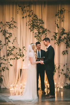 White draping covered with green vines as a ceremony backdrop, finished with candles on the floor. Floral Heaven at The Standard in Knoxville, TN | Bride Link