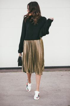 {Black sweater and gold pleated skirt.}