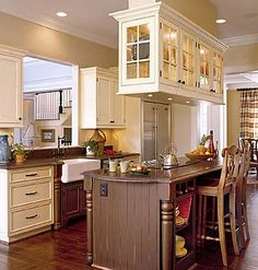 Country Kitchen    Distressed, furniture-style cabinetry in hues of cocoa and cream creates a casual atmosphere. The matte finish of the deep brown honed-granite countertops reinforces the aged appearance. Cabinets suspended over the island showcase a collection of colorful dishes. Glass doors and sides allow light to pass through, softening the visual impact of the cabinetry.