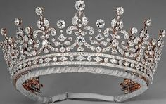 The Girls of Great Britain & Ireland Tiara. Consists of a diamond design of festoons and scrolls set on a bandeau base of round and lozenge-shaped diamonds, and toped with diamond collets. Originally a wedding gift to Queen Mary in 1893, it is now best recognized as Queen Elizabeth's crown of choice.