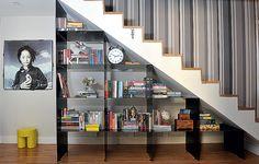 Para aproveitar o espaço sob a escada, os arquitetos Marcos Marcelino e Roberta Martins fizeram uma estante metálica para guardar livros e expor objetos de decoração