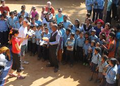 handing school supplies to Nepal village teacher volunteers