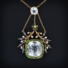 Aquamarine and demantoid garnet necklace, c. 1890. An exceptionally pale cushion shape aquamarine weighing 15 carats is surrounded by rich lime green Russian demantoid garnets and is further embraced by flowing branches of rose-cut diamonds and seed pearls topped by a demantoid flower. A smaller matching aquamarine facilitates the transition to the neckchain.
