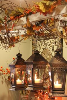 Lanterns w candles and vine with fall leaves.