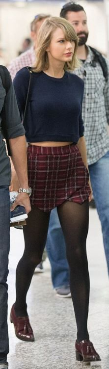 Who made  Taylor Swift's red plaid skirt, black leather handbag, blue sweater, and shoes?