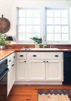 Black lampshades, fixtures, and appliances, white cabinets with butcher block counter tops. (More trim definition and curtains to break up the white mass.)