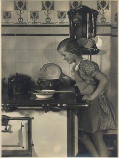 Originalfotografie von Ernst Schneider (1881-1959 Berlin): Junges Mädchen in der Küche um 1932 (bei dem dargestellten Mädchen handelt es sich um Ilse Buhl, die schon in jungen Jahre diverse Titelblätter als Kinderstar schmückte, auf dem Foto dürfte sie ca. 8 Jahre sein. Ilse Buhl war später auch als Schauspielerin tätig). Verso gestempelt Ernst Schneider, Berlin