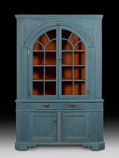 "probably Duchess County, New York, ca 1750 to 1810, of pine and poplar, painted and glazed in blue-gray paint over an earlier blue. The moulded cornice above an applied rope moulding, over an applied arch with foliates on either side and arched glazed doors opening to three shaped shelves, all on a projecting moulded base with hinged doors with moulded recessed panels, over spurred bracket feet; 92.50"" high x 62"" wide x 32"" deep."