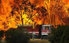 A fire truck moves away from out of control flames from a bushfire in the Bunyip Sate Forest near the township of Tonimbuk, 125 kilometers (78 miles) west of Melbourne, Saturday, Feb. 7, 2009. Walls of flame roared across southeastern Australia, razing scores of homes, forests and farmland in the sunburned country's worst wildfire disaster in a quarter century.