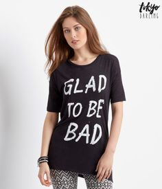 "Being as crazy-cool as you are requires some serious talent, so get some recognition for your wild ways in this eye-catching Tokyo Darling Bad Tee! ""Glad to be Bad"" text is stylized with distressed letters on the front for some seriously edgy flair.<br><br>Relaxed fit. Approx. length: 28""<br>Style: 4739. Imported.<br><br>80% rayon, 20% cotton.<br>Machine wash/dry flat.<br><br>Model height: 5'10""; Size: Small."