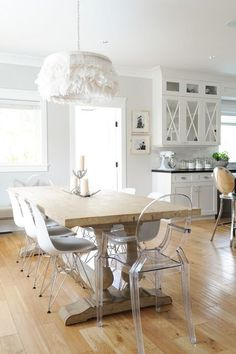 Chic dining room boasts a white feather chandelier hanging over a reclaimed wood baluster dining table lined with Ghost Chairs and Eames Molded Plastic Chairs.
