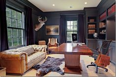 I love this mix: Chesterfield sofa in well worn golden leather, a contemporary desk in red hued tropical wood with high gloss finish, the modern office chair hung with leather satchel (acts as a desk drawer?), the sisal rug ... and the dark walls.