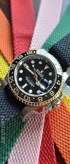 Rolex Oyster Perpetual GMT-Master II in steel & 18k yellow gold, shown on a rainbow of military style NATO straps. Change up your look!