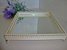 Bandeja com base de MDF, pintada e vernizada. Decorada com meia pérola e strass dourado. Fundo de espelho. Pés egípcios.
