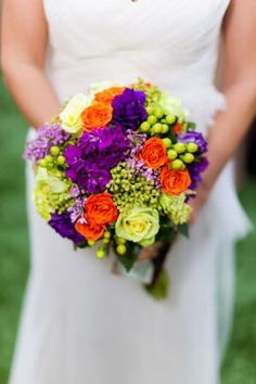 "This beautiful bridal bouquet is made of bright orange, purple and jade roses, purple stocks and lilacs. ""My dad planted a lilac for me every year on my birthday. Since my parents passed away a few years ago, this was the way for me to bring them into the wedding and have them there with me,"" says one of the brides."