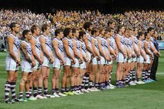 The Fremantle Dockers line up during the national anthem.