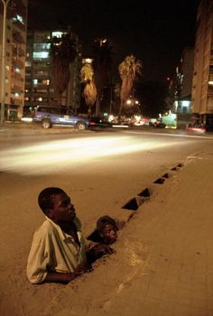 Chris Steele-Perkins I  ANGOLA. Street Children in Luanda. Street kids come out from the sewer to the street at night. 1999.