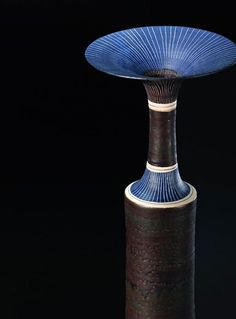 scandinaviancollectors: LUCIE RIE, Cylindrical vase with a flaring neck, 1976. Material porcelain, dark brown manganese glaze, blue shoulder and lip, sgraffito and inlaid blue bands. / Phillips