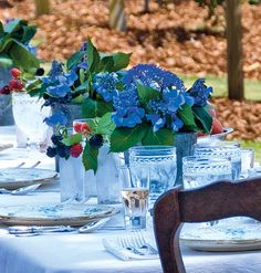 Galvanized steel buckets and mason jars hold casual arrangements of hydrangeas and berries for a cool, summer setting.